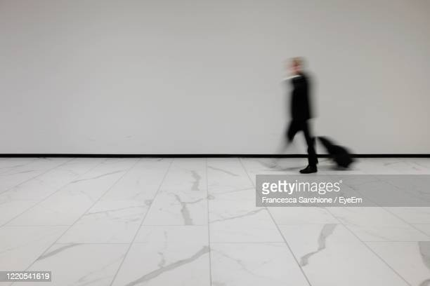 blurry man with suitcase at the airport - defocussed stock pictures, royalty-free photos & images