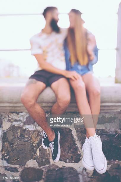 Unscharfem romantische hipster-Paar auf einer Steinmauer Hände halten