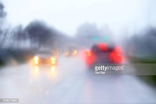 blurry traffic scene through windshield during heavy afternoon rain in florida - zen rial stock photos and pictures