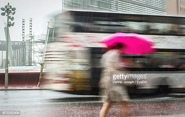 Blurry View Of Woman Walking On Sidewalk In The Rain