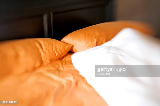 blurry wooden bed with white and orange linens - dana white stock pictures, royalty-free photos & images
