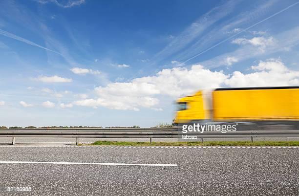 amarillo camión en la carretera, desenfoque, espacio de copia. cielo azul. - estela grande fotografías e imágenes de stock
