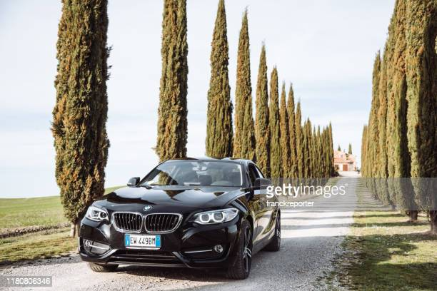 bmw 2 series coupe parked on the countryside road in pienza - bmw stock pictures, royalty-free photos & images