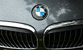 Bmw motor company badge on the front from a black car. BMW is a German automobile, motorcycle and engine manufacturing company founded in 1916