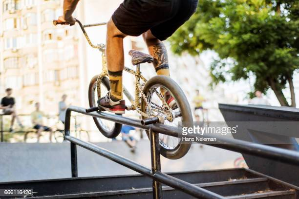 bmx rider performing bicycle stunt - bmx cycling stock pictures, royalty-free photos & images