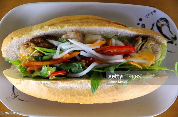 Bánh mì (Vietnamese baguette) containing pork belly, pickled carrots and daikon (white radish), red chilli, lettuce, fresh mint and coriander leaves