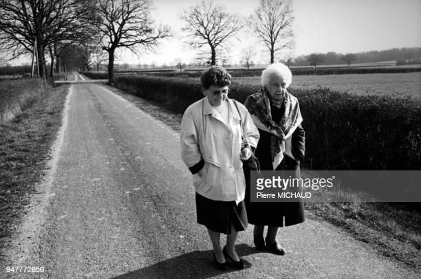 Bénévole d'une association d'aide au troisième âge se promenant avec une femme âgée en France
