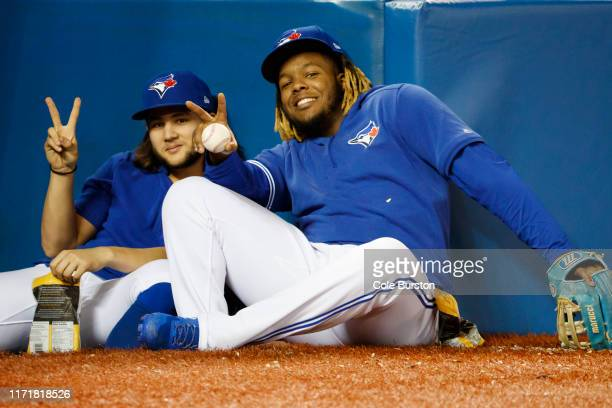 Bo Bichette and Vladimir Guerrero Jr. #27 of the Toronto Blue Jays sit in the dugout during the ninth inning of their MLB game against the Tampa Bay...