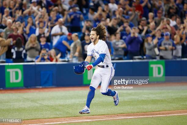 Bo Bichette of the Toronto Blue Jays celebrates as he runs into home plate after hitting a solo home run to score the winning run in the twelfth...