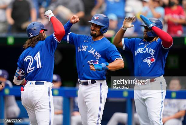 Bo Bichette of the Toronto Blue Jays celebrates his three-run home run with teammates Marcus Semien and Vladimir Guerrero Jr. #27 in the first inning...