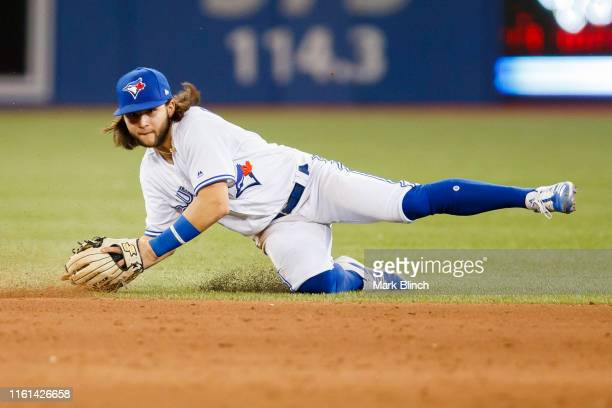 Bo Bichette of the Toronto Blue Jays dives for a ball against the Texas Rangers in the ninth inning during their MLB game at Rogers Centre on August...