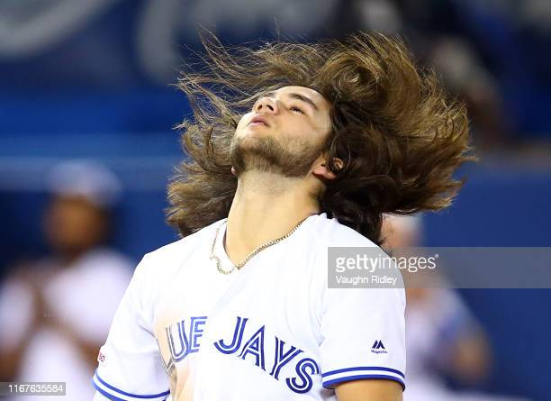 Bo Bichette of the Toronto Blue Jays flicks his hair back after scoring a run on a triple by Cavan Biggio in the fifth inning during a MLB game...