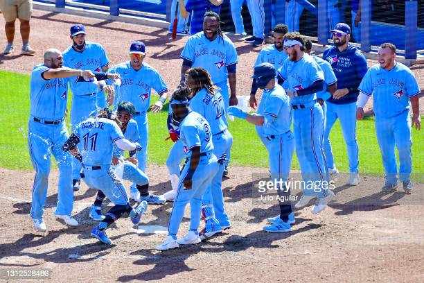Bo Bichette of the Toronto Blue Jays gets water poured on him from Rowdy Tellez after hitting a walk-off home run against the New York Yankees in the...