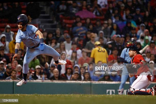 Bo Bichette of the Toronto Blue Jays goes airborne after being tagged out by catcher Christian Vazquez of the Boston Red Sox during the first inning...