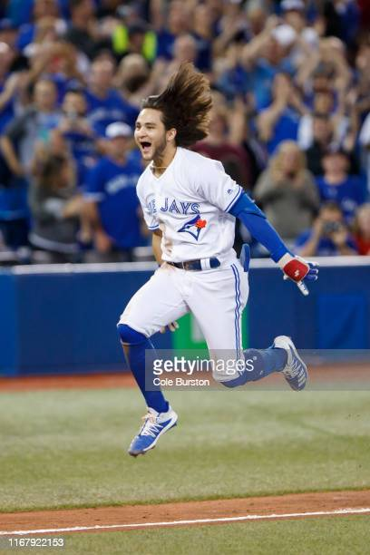 Bo Bichette of the Toronto Blue Jays leaps as he runs into home plate, after hitting a home run to score the winning run in the twelfth inning of...