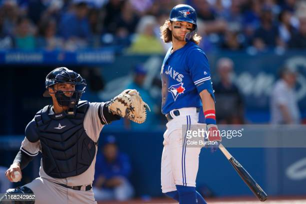 Bo Bichette of the Toronto Blue Jays reacts alongside Kyle Higashioka of the New York Yankees as he takes a strike in the third inning of their MLB...