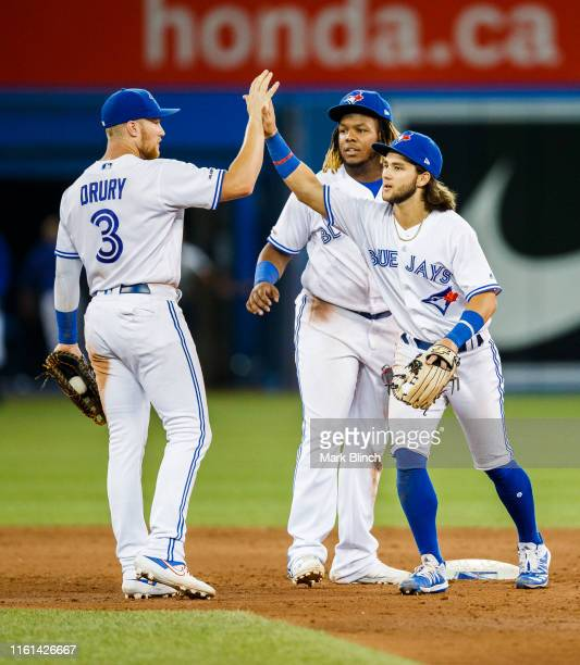 Bo Bichette Vladimir Guerrero Jr #27 and Brandon Drury of the Toronto Blue Jays celebrate defeating the Texas Rangers in their MLB game at Rogers...
