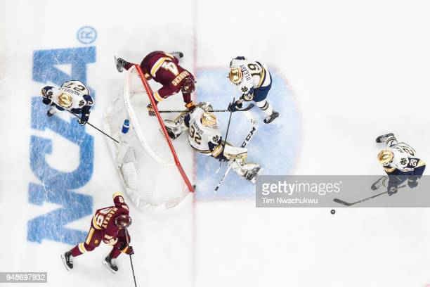 Bo Brauer of the Notre Dame Fighting Irish clears the puck against the MinnesotaDuluth Bulldogs during the Division I Men's Ice Hockey Championship...