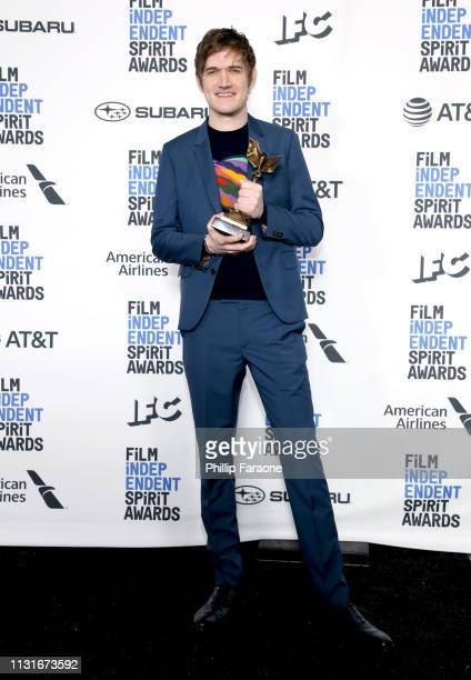 """Bo Burnham poses in the press room with the Best First Screenplay award for the film """"Eighth Grade"""" during the 2019 Film Independent Spirit Awards on..."""
