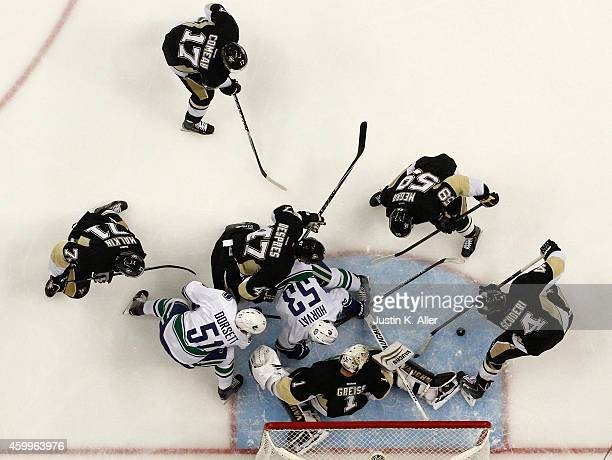 Bo Horvat and Derek Dorsett of the Vancouver Canucks battle for the puck against goalie Thomas Greiss of the Pittsburgh Penguins during the game at...