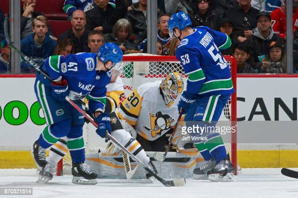 Bo Horvat and Sven Baertschi of the Vancouver Canucks look on as Matthew Murray of the Pittsburgh Penguins makes a save during their NHL game at...