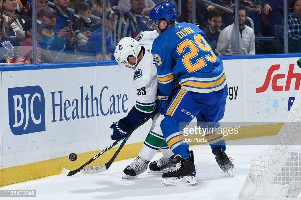 Bo Horvat of the Vancouver Canucks and Vince Dunn of the St Louis Blues battle for the puck at Enterprise Center on April 6 2019 in St Louis Missouri
