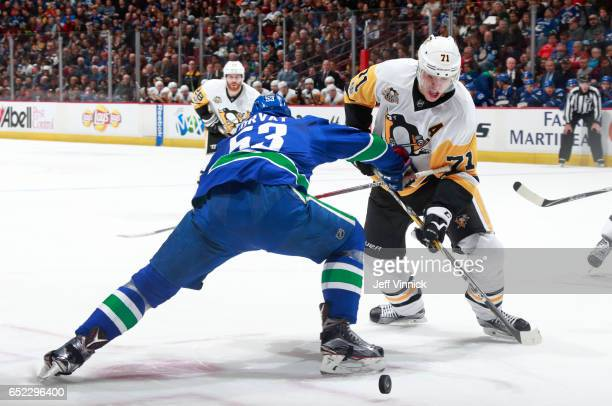 Bo Horvat of the Vancouver Canucks checks Evgeni Malkin of the Pittsburgh Penguins during their NHL game at Rogers Arena March 11, 2017 in Vancouver,...