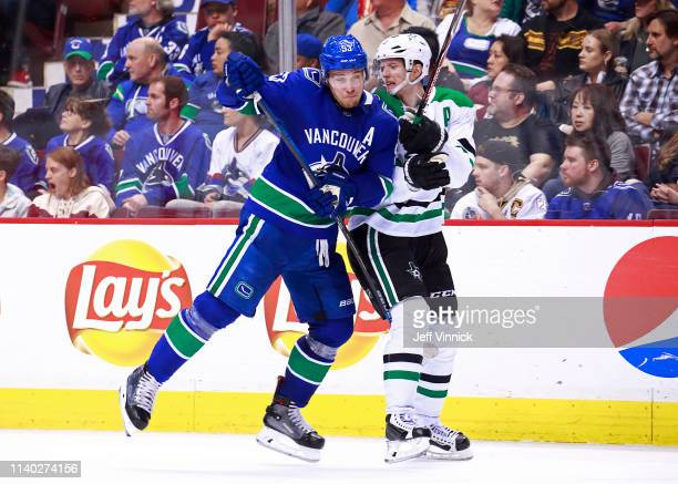Bo Horvat of the Vancouver Canucks checks John Klingberg of the Dallas Stars during their NHL game at Rogers Arena March 30 2019 in Vancouver British...