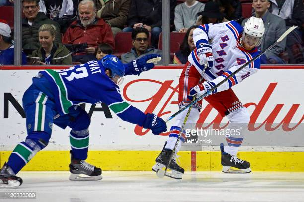 Bo Horvat of the Vancouver Canucks checks Marc Staal of the New York Rangers during their NHL game at Rogers Arena March 13 2019 in Vancouver British...