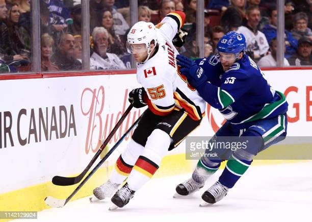 Bo Horvat of the Vancouver Canucks checks Noah Hanifin of the Calgary Flames during their NHL game at Rogers Arena March 23 2019 in Vancouver British...