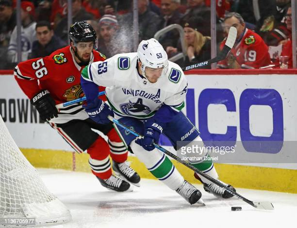 Bo Horvat of the Vancouver Canucks controls the puck in front of Erik Gustafsson of the Chicago Blackhawks at the United Center on March 18 2019 in...