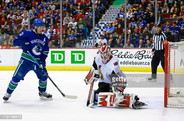 Bo Horvat of the Vancouver Canucks looks on as teammate Brock Boeser scores on Anders Nilsson of the Ottawa Senators during their NHL game at Rogers...