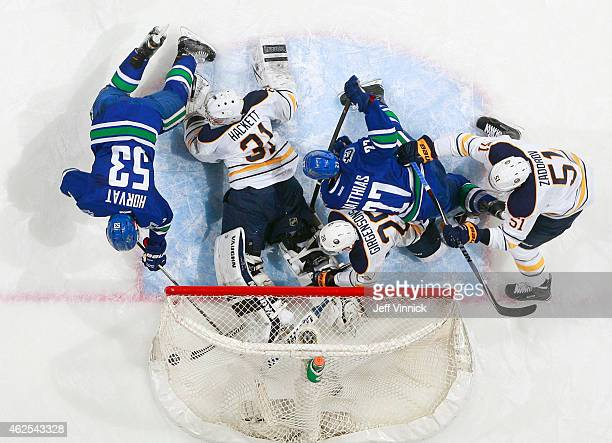 Bo Horvat of the Vancouver Canucks scores on Matt Hackett of the Buffalo Sabres with Zemgus Girgensons and Nikita Zadorov of Buffalo joining Shawn...
