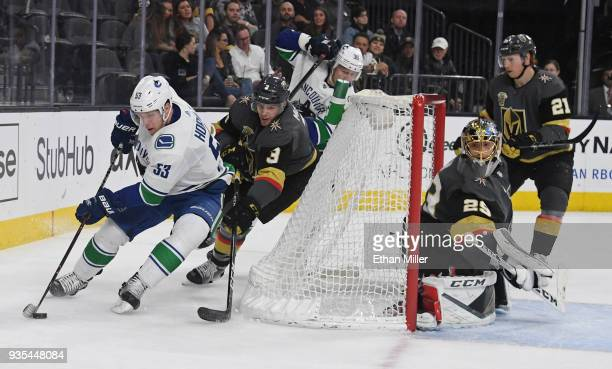 Bo Horvat of the Vancouver Canucks skates with the puck against Brayden McNabb of the Vegas Golden Knights as MarcAndre Fleury of the Golden Knights...