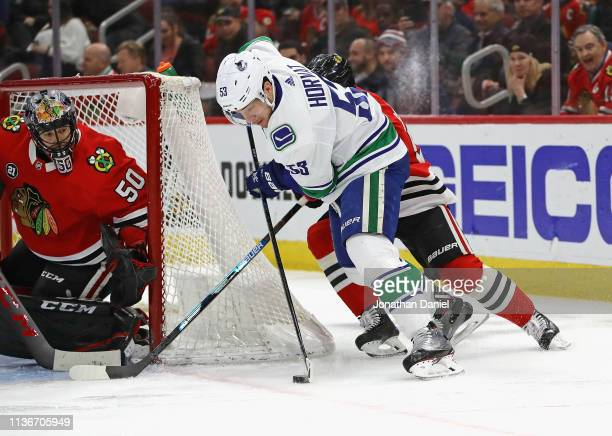 Bo Horvat of the Vancouver Canucks tries to get off a shot against Corey Crawford of the Chicago Blackhawks as Erik Gustafsson applies pressure at...