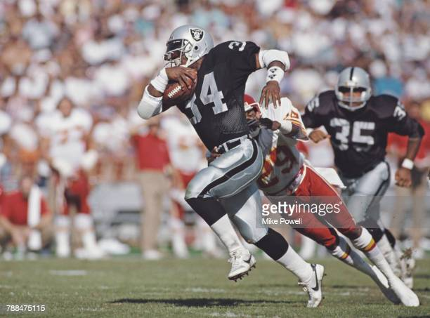 Bo Jackson Full Back for the Los Angeles Raiders dodges a tackle attempt by Albert Lewis defensive back for the Kansas City Chiefs during their...