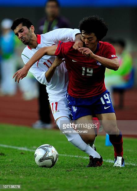 Bo Kyung Kim of South Korea holds off a challenge from Mohsen Mosalman of Iran in the Men's Bronze Medal between South Korea and Iran at Tianhe...