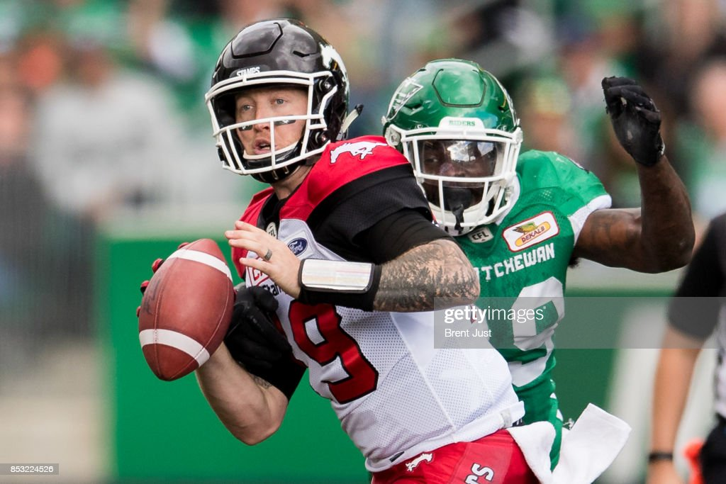 Bo Levi Mitchell #19 of the Calgary Stampeders is about to be sacked by A.C. Leonard #99 of the Saskatchewan Roughriders in the second half of the game between the Calgary Stampeders and Saskatchewan Roughriders at Mosaic Stadium on September 24, 2017 in Regina, Canada.