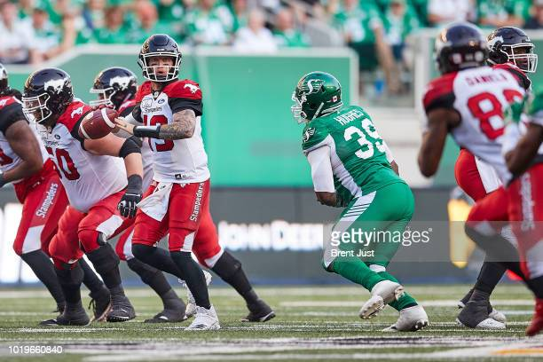Bo Levi Mitchell of the Calgary Stampeders looks for a receiver while under pressure from Charleston Hughes of the Saskatchewan Roughriders in the...