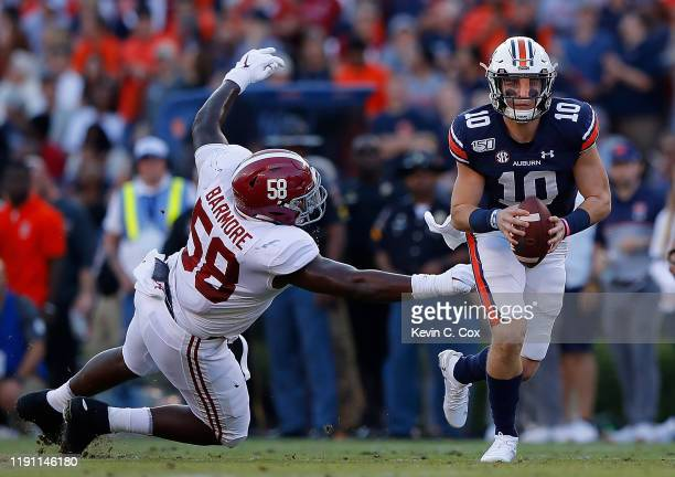 Bo Nix of the Auburn Tigers breaks a tackle by Christian Barmore of the Alabama Crimson Tide in the first half at Jordan Hare Stadium on November 30,...