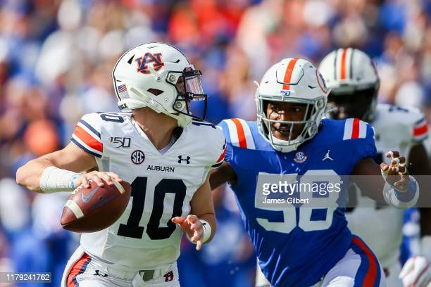 Bo Nix of the Auburn Tigers is pressured by Jonathan Greenard of the Florida Gators during the first quarter of a game at Ben Hill Griffin Stadium on...