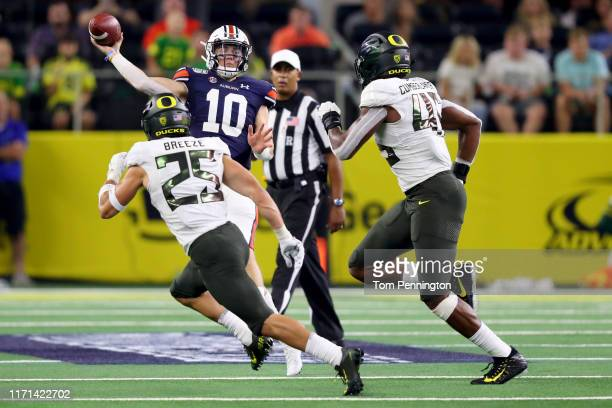 Bo Nix of the Auburn Tigers looks for an open receiver against Brady Breeze of the Oregon Ducks and Gus Cumberlander of the Oregon Ducks in the...