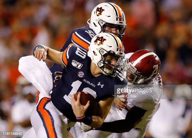 Bo Nix of the Auburn Tigers rushes against Jared Mayden of the Alabama Crimson Tide in the second half at Jordan Hare Stadium on November 30 2019 in...