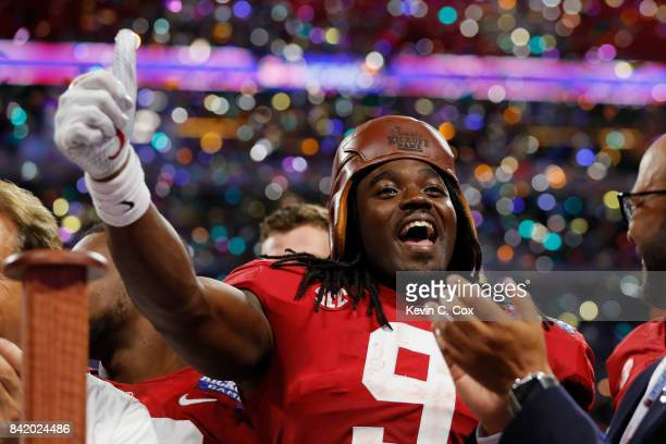Bo Scarbrough of the Alabama Crimson Tide celebrates with the Chick-fil-A Kick-Off Game trophy after defeating the Florida State Seminoles 24-7 in...
