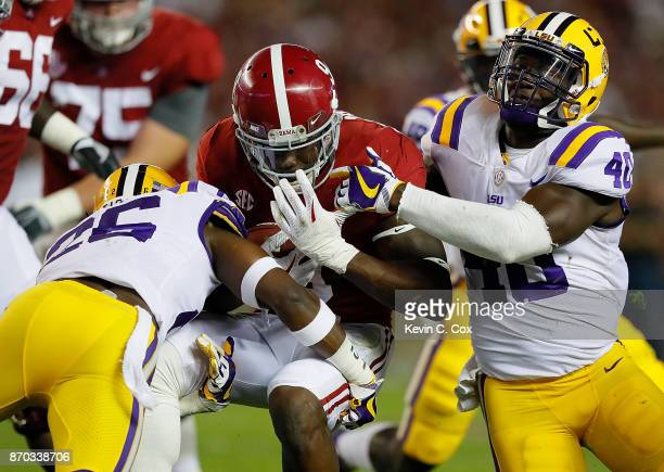 Bo Scarbrough of the Alabama Crimson Tide is tackled by John Battle and Devin White of the LSU Tigers at BryantDenny Stadium on November 4 2017 in...