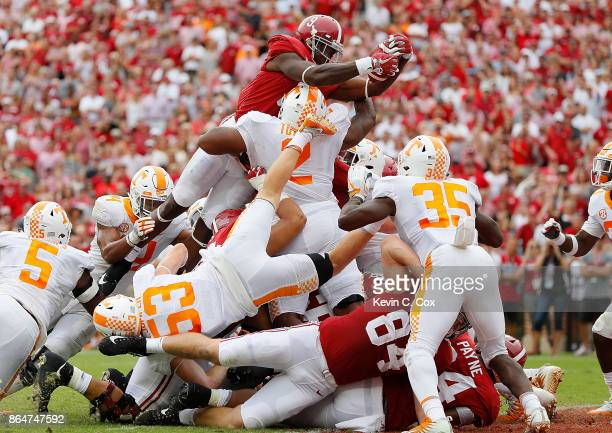 Bo Scarbrough of the Alabama Crimson Tide leaps over Shy Tuttle of the Tennessee Volunteers for a touchdown at BryantDenny Stadium on October 21 2017...