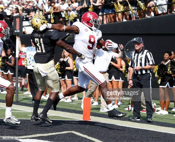 Bo Scarbrough of the Alabama Crimson Tide pushes aside Tre Herndon of the Vanderbilt Commodores to score a touchdown against the Commodores during...