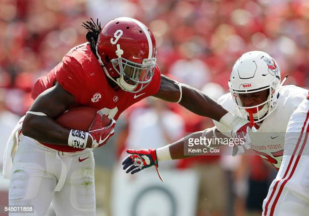 Bo Scarbrough of the Alabama Crimson Tide rushes against Juju Hughes of the Fresno State Bulldogs at Bryant-Denny Stadium on September 9, 2017 in...