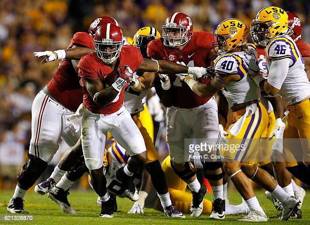 Bo Scarbrough of the Alabama Crimson Tide rushes away from Duke Riley and Tashawn Bower of the LSU Tigers at Tiger Stadium on November 5 2016 in...