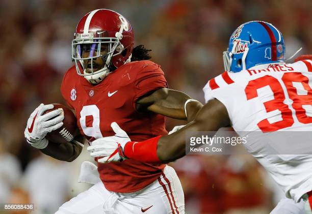 Bo Scarbrough of the Alabama Crimson Tide rushes away from Marquis Haynes of the Mississippi Rebels at BryantDenny Stadium on September 30 2017 in...